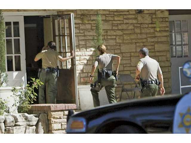Members of the SCV Sheriff's Department enter the Tony Alamo Christian Church after gunshots were reported near the compound Thursday afternoon. Officers checked the building but did not find any suspects or injured persons. The surrounding areas were also investigated but turned out inconclusive.