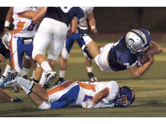 Saugus quarterback Zack Gauthier dives over a Westlake player Sept. 17.