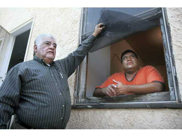 Pastor Ismael Estrada, left, and Juan Ramirez show where an unknown suspect broke into New Life Apostolic Church in Val Verde on Sunday night. The suspect took music equipment, speakers and money offerings from the church.