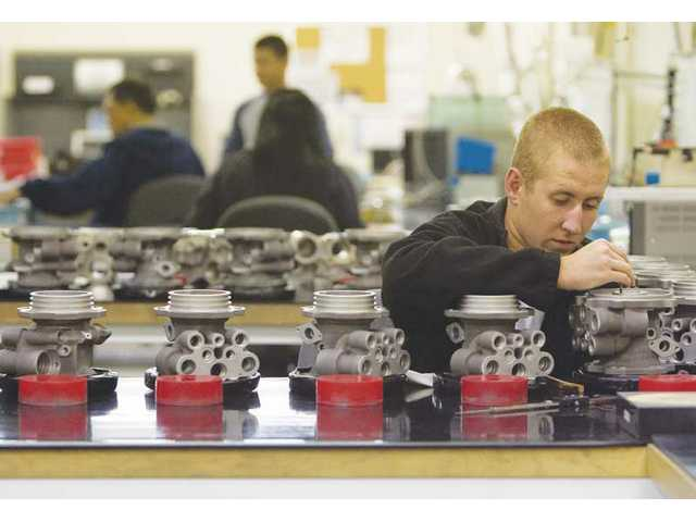 Corey Benoit, inspects a manifold valve at the final inspection station at the B & B Manufacturing company on Wednesday morning.