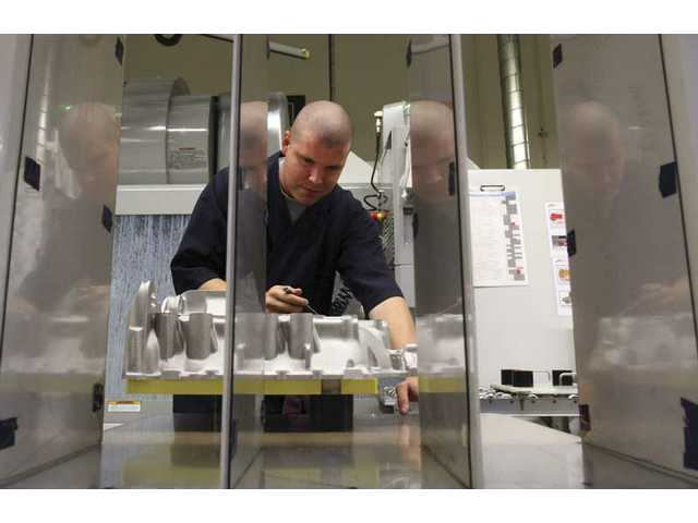 Victor Reyes, machine specialist, inspects an aircraft enginee at the B & B Manufacturing company Wednesday morning.