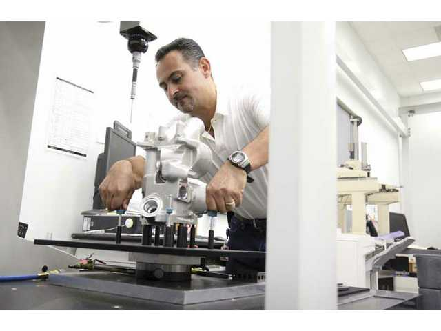 Fernando Gonzales, inspector supervisor at B & B Manufacturing, uses computer-operated machinery to inspect parts of an aircraft engine on Wednesday morning.