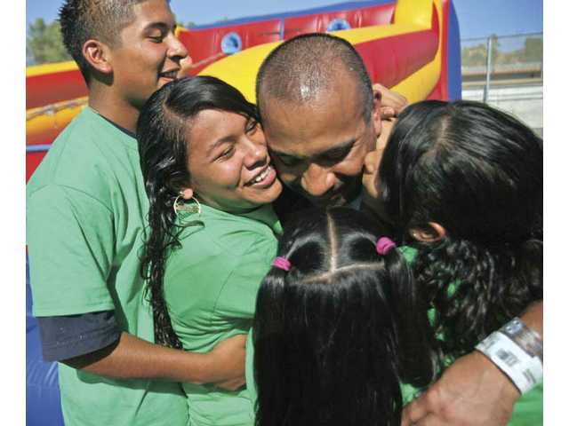Pitchess Detention Center inmate Angel Guerrero is buried in hugs and kisses from his kids during the Returning Hearts event Friday afternoon. Graduates of the MERIT Program were able to spend the afternoon with their children and family members.