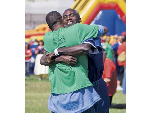 Derek Hodge hugs his 16-year-old son Cornelius Hodge at the Returning Hearts event Friday afternoon. The event, hosted by Grace Baptist Church, allows MERIT program graduates to spend a whole afternoon with their young family members.