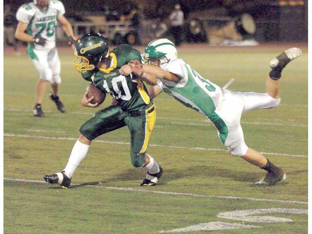 Canyon wide receiver Shane Habberstad (10) drags Thousand Oaks' Mark Lister for extra yardage Friday at Harry Welch Stadium at Canyon High.