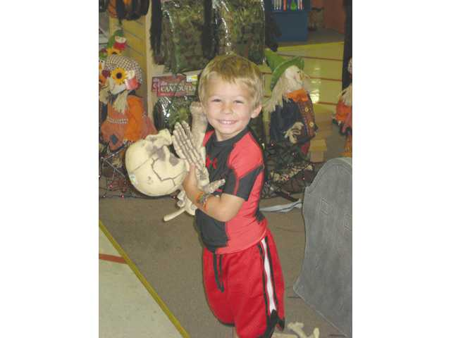 Three-year-old Donovan Dunn clutches bones and a skull, common indoor and outdoor Halloween decorations.