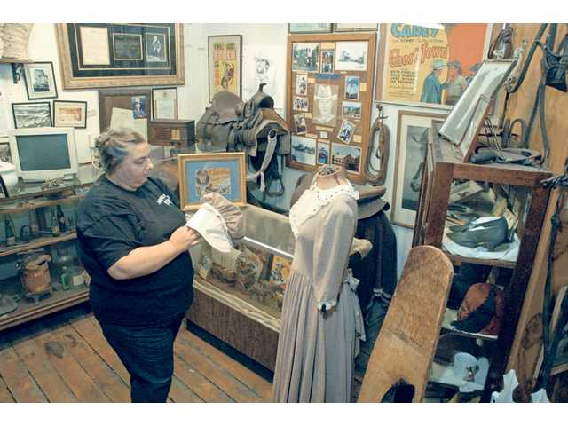 Saletore primps the bonnet of a period style woman's dress on display at the SCV Historical Society. Among the historic treasures are items from SCV film history, which include Hoot Gibson's saddle. The museum is open Saturdays and Sundays 1 to 4 p.m.