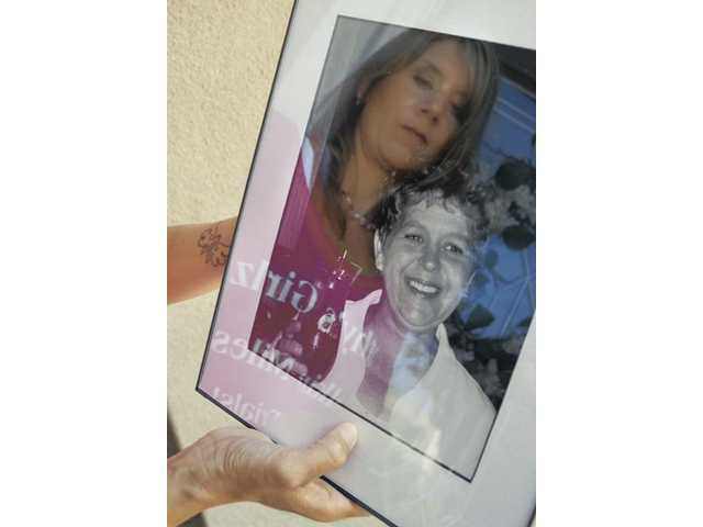 Kelly Iles holds a photo of her mother, Kathy Clements, who died of breast cancer on June 3. Iles is reflected in the glass. Her left wrist sports a tattoo in remembrance of her mother.
