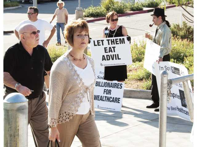 "Santa Clarita resident Lissa Tegelman, as ""Ivana Profit,"" and Palmdale resident Gene Truex, as ""Richoff Jersikness,"" in background with signs, dress up as health care billionaires to make a point for attendees of Congressman Howard P. ""Buck"" McKeon's health care town hall held in the College of the Canyons gymnasium Saturday."