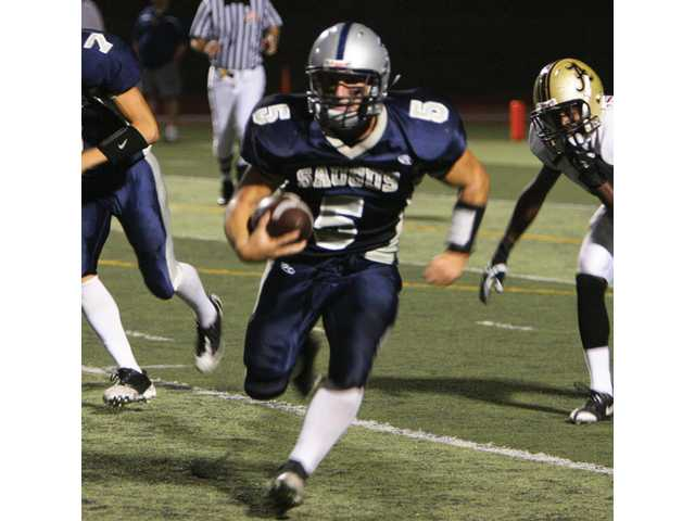 Saugus running back Ryan Zirbel rushes through the Alemany defense in the second quarter Friday night at College of the Canyons.