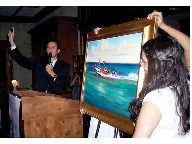 "Sotheby's auctioneer Blake Koh takes bids for ""Rush Hour"" by George Scribner."