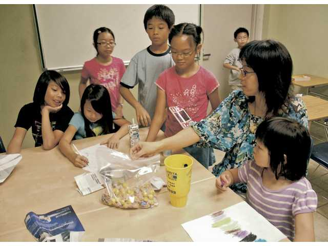 Huifang Li, right, works with students as their parents attend an orientation meeting at SCV Chinese School on Sept. 26.