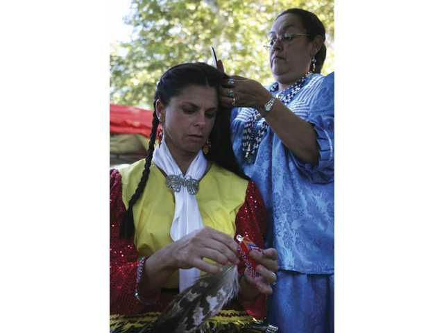 Lisa Friesen, from Orange County,has her braided in preparation for the Grand Entrance to the Arena, during the 15th Annual American Indian Powwow celebration at Hart Park on Saturday afternoon.