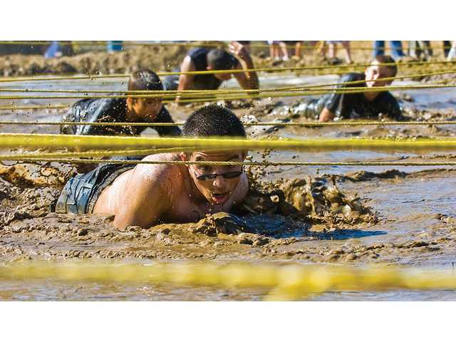 Competitors struggle through one of many mud pits at Sunday's 13th annual Mud Run, hosted by the Sheriff's Enforcement Bureau at Pitchess Detention.