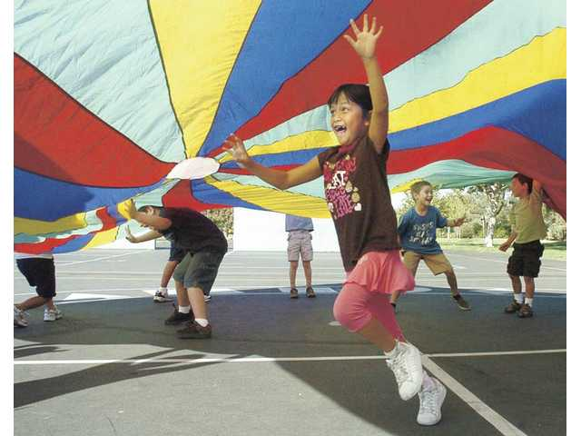 Second-grader Mia Chiamthamachinda runs under a lifted parachute Thursday as part of a creative physical education program at Valencia Valley Elementary School.