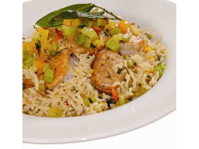 Shrimp & Sausage Cajun JambalayaMakes 12 to 15 servings for about $3.15 per serving1 1/2 large onions, finely chopped2 bunches scallions1/2 cup chopped cilantro2 stalks celery, diced1/2 green or yellow bell pepper, diced1 1/2 teaspoons minced garlicKosher salt, fresh cracked black pepper2 to 3 teaspoons cayenne pepper1 1/2 pounds Members Mark Garlic Sausage (or hot links, Andouille, etc.) 1/3 cup vegetable oil5 bay leaves7 1/2 cups chicken broth1 pound Members Mark Jumbo ready to cook shrimp (about 36) defrosted3 3/4 cups long grain white rice (or jasmine or basmati) Finely dice vegetables and put into large flat pan. Liberally dust with kosher salt, cracked black pepper and cayenne pepper. Set aside. Slice sausage into 1/4-inch discs. In heavy (preferably cast iron) skillet over medium high heat, add oil, then sauté sausage slices until browned. Remove from pan with a slotted spoon. Add in diced vegetables; lower heat to medium, and sauté until well browned. Remove from heat. Combine chicken broth, browned sausage, bay leaves and vegetables in stockpot and taste for salt and pepper (black and cayenne). Bring to a boil, add rice and return to a boil for one minute. Lower heat to medium low and add shrimp. Stir to mix and cover. Cook until rice is barely done and has absorbed the liquids, about 25 minutes. Serve immediately or let cool then refrig­erate, or freeze. To serve: defrost in the refrigerator, then reheat over low on the stovetop.