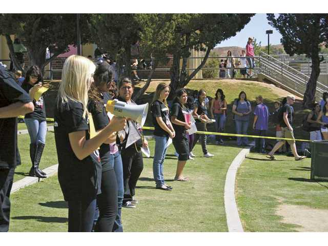 "Canyon High School student Ruby Lawler participates in an on-campus ""Die-In"" event on Sept. 22 to promote  global awareness about children's rights violations. Students gathered to watch the demonstration during their lunch break."