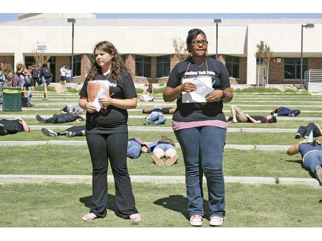 "Canyon High School students Shanley Newman, left, and Aysa Jackson were two of the seven demonstrators who ""survived"" during the event. Those who ""died"" are  lying on the grass behind."