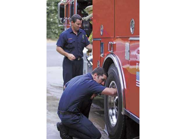 Martin Maher, kneeling, and Steve Betteridge clean a fire engine at Station 123 in Canyon Country on Tuesday afternoon. Station 123, along with other local stations, have moved from Battalion 6 to Battalion 22. The station will continue serving the Santa Clarita Valley.