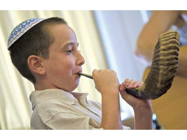 "Eight-year-old Daniel Bratslavsky blows into a ram ""Shofar"" during Temple Beth Ami's Yom Kippur service for children at the Hyatt Regency Valencia on Monday morning."