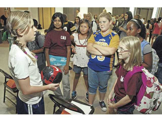 "Camryn Utvich, left, of Castaic Middle School, holds a soccer ball as she gives an oral history of USA Olympic soccer team gold medalist Mia Hamm for a group of her schoolmates. The wax ""figures"" were 115 sixth-grade students who gave a short presentation on his or her chosen hero when activated."