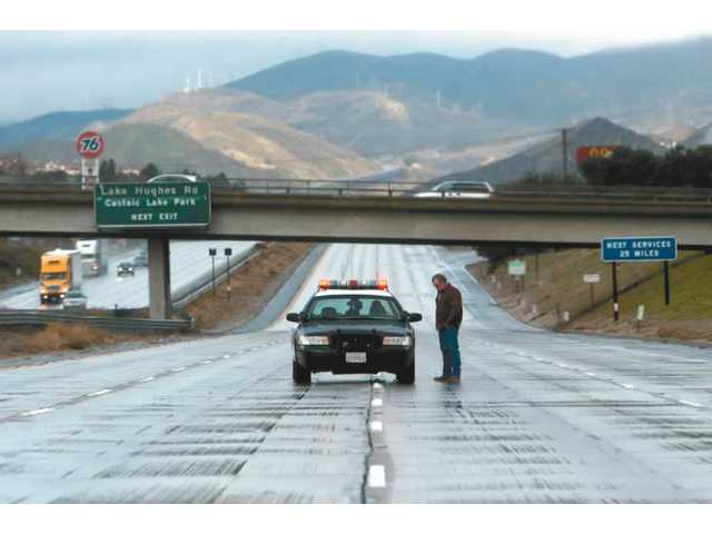 A man asks a CHP officer about the status of the Interstate 5 closure Thursday morning. Snow forced officials to close the route through the Grapevine, leaving many stranded in Castaic and Kern County near Parker Road.03