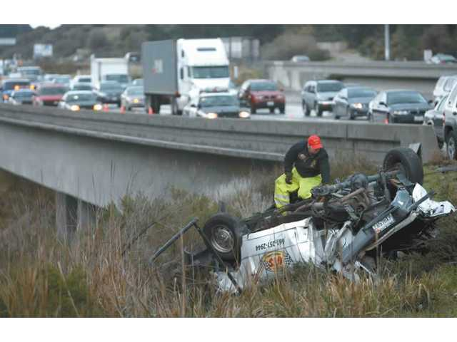A tow truck driver connects his chain to an overturned pickup truck. The truck had collided with a Honda CR-V and a semi truck at 11:33 a.m, then slid down an embankment off of northbound Interstate 5, near The Old Road.