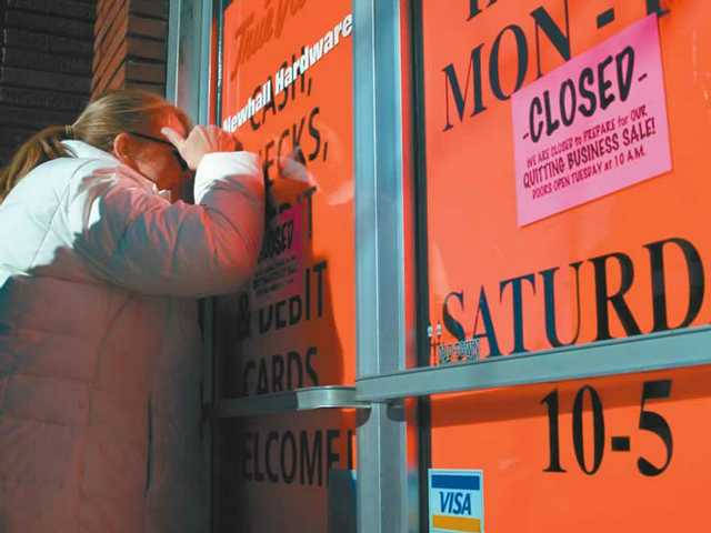 Laura Wambsgans of Valencia peers into the closed Newhall Hardware store on Monday. The store is closed to prepare for its liquidation sale and will reopen today at 10 a.m. It will stay open until the liquidation is complete.