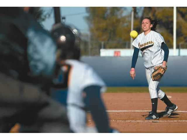 College of the Canyons pitcher Sara Campos, right, delivers a pitch to catcher Whitney Stanley, center, in the Cougars' 8-0 loss to Long Beach City College Wednesday at home.