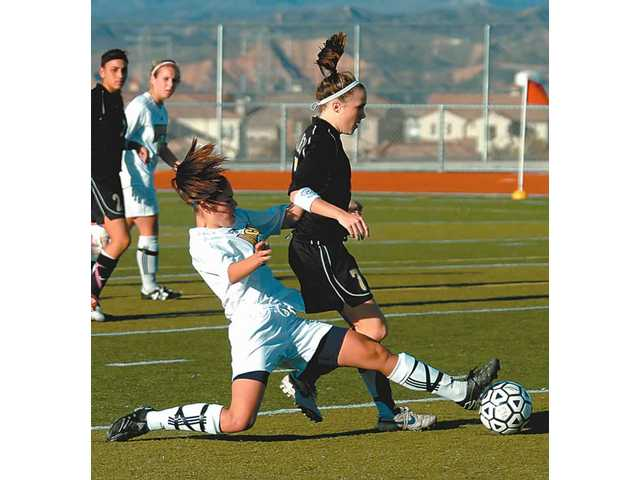 West Ranch freshman Amanda Dailor, left, slides to kick the ball away from Valencia's Makayla Hambek (7) in the first half Thursday at West Ranch High. The Wildcats topped the Vikings 2-0 for their third league win of the year.