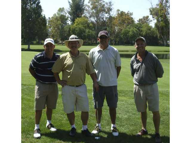Charlie Rasmussen, president of C.A. Rasmussen Inc. (center front), stands with golfing teammates (left to right) Tom Charon, Jesus Garcia and John Spalione during the 18th Annual COC Foundation Golf Tournament at Valencia Country Club. The event raised more than $90,000 to help fund student aid programs.