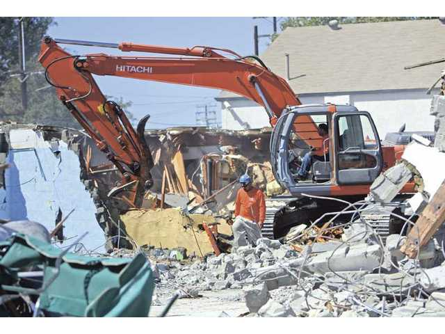 Unlimited Environmental Inc. employee Richard Miller demolishes what used to be the White Light Chiropractic office on Spruce Street in Newhall on Wednesday while co-worker Ralph Pineda walks around the rubble. The building is being cleared for the future site of the Newhall Library expected to be completed in 2012.