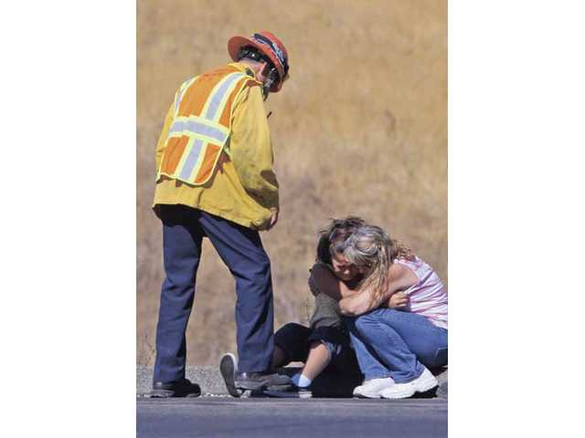 Two females embrace on the side of the I-5 freeway at the scene of the fatal traffic collision.