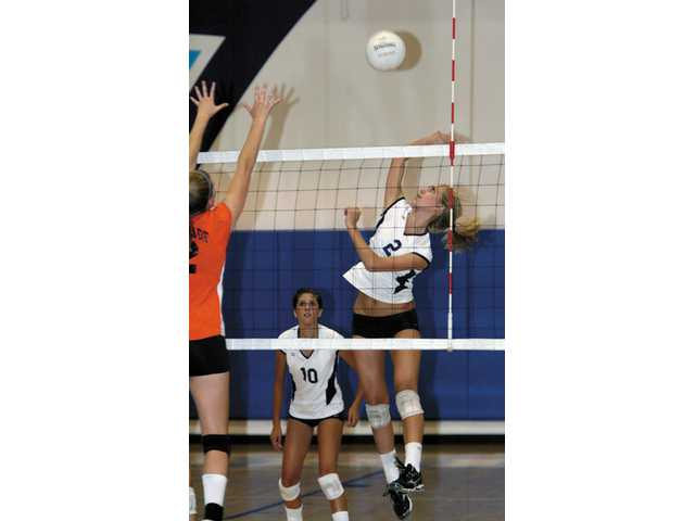 Kacie Crawford prepares to spike a ball for Saugus on Wednesday against Chaminade. Jaclyn Clark looks on.