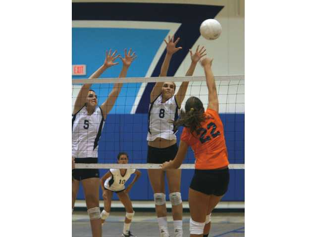 Saugus outside hitter Katie Estes, right, makes a block on Heather Garcia of Chaminade as Rachel Kempler jumps with her on Wednesday in the Centurions' three-set win at Saugus High School. Jaclyn Clark, rear, looks on.