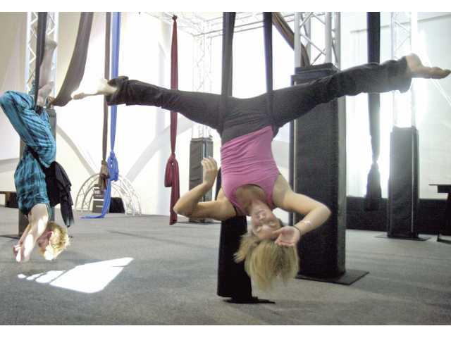 Kinsley Johnson, right, and Debbie Park, far left, perform a suspended yoga pose during a Vozdu class at Valencia's Aerial Experience Productions.