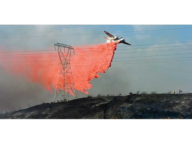 An air tanker drops fire retardant on the Crossover Fire on Wednesday. Arcing electrical wires made the fire difficult to fight. The blaze burned more than 75 acres.