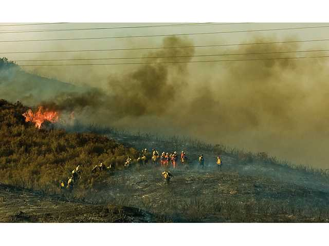 Firefighters traverse rugged terrain to fight the Crossover Fire on Wednesday. Arcing electrical wires kept fire crews at bay early in the battle.