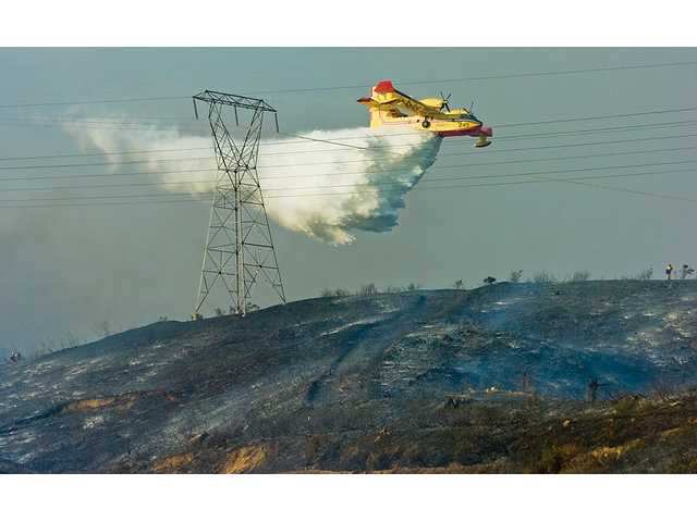 A SuperScooper drops water on the Crossover Fire Wednesday. The SuperScooper refilled at Castaic Lake during the afternoon blaze that burned more than 75 acres along Interstate 5.