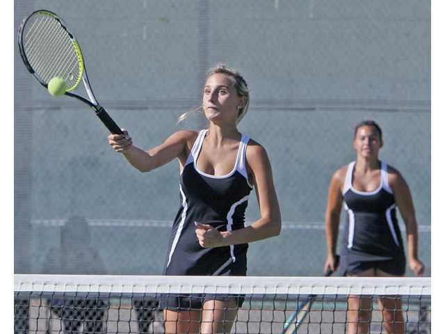 Hart tennis players Ingrid Jelderks, left, returns a shot Thursday as teammate Amber Bock looks on at Canyon High. The pair won all three sets.