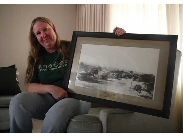 Maggi Perkins, grandaughter of famous SCV Historian Arthur B. Perkins, holds a picture of what Downtown Newhall looked like in the early 1900s. Although selling and donating a variety of items, the Perkins family are keeping numerous items as well.