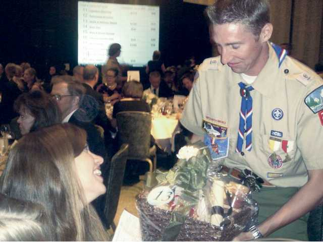 "Curtis Vangrinsven, 17, a Boy Scout for the past 11 years, displays the ""Gardening Basket"" auction item to guest, Jackie Sisolak at the fourth annual Leaders of Character dinner held at the Hyatt Regency Valencia to honor Dr. Joseph and Barbara Schulman, Bill and Cathy Kennedy and Rick and Ann Patterson. The three SCV couples are the 2009 Leaders of Character named by the Boy Scouts of America."