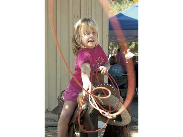 Hailey Hartigan, 6, tries her hand at calf roping, one of the events for kids at the cook-off.
