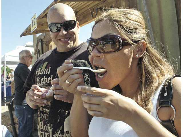 Raul Estrada, left, watches Jessica Herrera sample the intensity of the Desert Critter Chili at the L.A. County Sheriff's Fun in the Sun Chili Cook-off at Jack Bones Equestrian Center in Castaic on Sunday. Attendees were given the opportunity to sample 16 chili recipes.