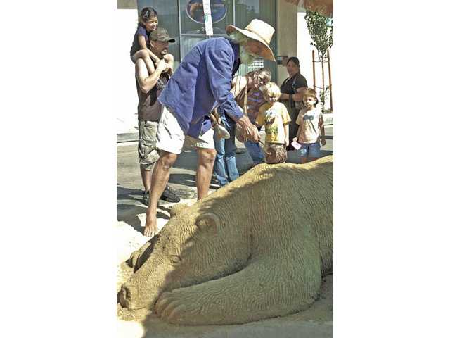 Passers-by stop to watch artist Dennis Shives sculpt a giant sleeping bear in sand at the Santa Clarita Festival of the Arts held Saturday on Main Street in Old Town Newhall.