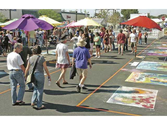People walk along Main Street as they enjoy the works of art at the festival.