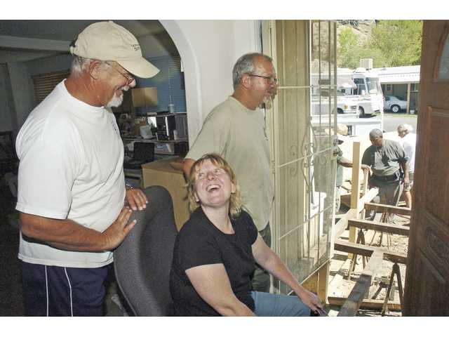 Santa Clarita Valley Senior Center Handyworker program leader Frank Pascoe, left, chats with Jennifer Duke and Errol Adams recently as handymen work on their new porch. The Handyworker program helps low-income homeowners with repair projects.