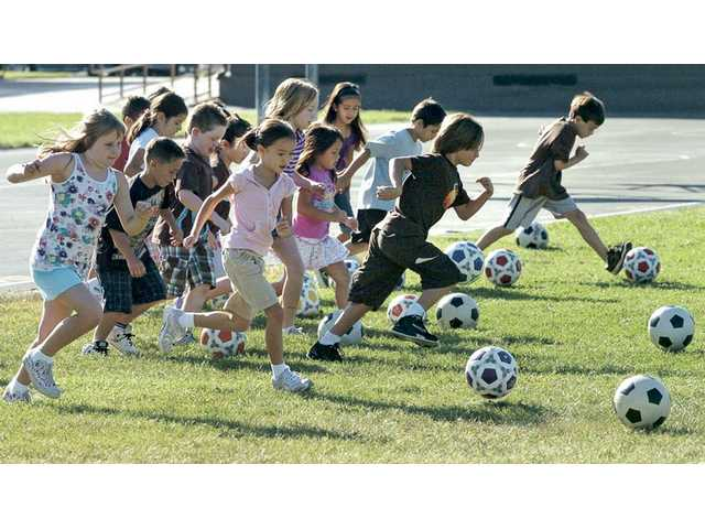 Second-graders race against one another Thursday as part of a creative P.E. exercise program at Valencia Valley Elementary School.