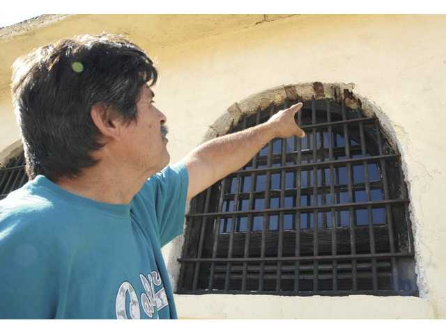 Manny Santana, who owns the jail in Newhall, points at one of the windows he claims have developed some cracks due to demolition crews removing nearby buildings on Friday.