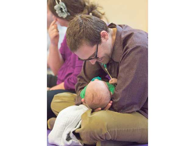 Ryan Hedegard plays with 10-week-old son Jack during the seminar.